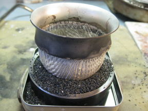 The foot is protected by carborundum grain while the rim is soldered on from the inside.